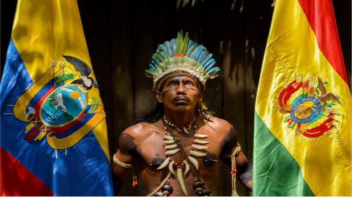 Un ciudadano Tikuna entre las banderas de Bolivia y Colombia en un encuentro de líderes presidenciales.