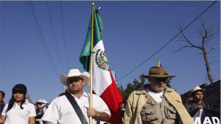 Julián LeBarón sostiene la bandera de México en la Caravana por la Paz